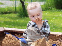Child exploring. Baby boy playing at the sandy playground Stock Image