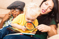 Child exploring book. Young women and children reading book with magnifying glass Royalty Free Stock Photo