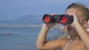 Child exploring the sea with binoculars. Boy standing on the beach and looking at the sea through binoculars stock video footage