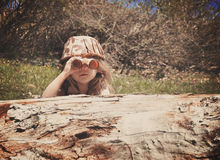 Child Exploring in Woods. A little girl is hiding behind an old log in the woods with a camouflage hat and binoculars searching and playing for an imagination or stock photo