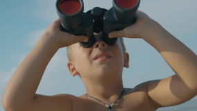Child exploring the world with binoculars stock footage