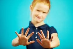 Child expresses denial by pulling his hands into the camera, showing repulsion or rejection. Squeamish girl doesn`t want to get anything Royalty Free Stock Photography