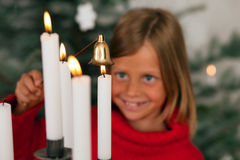 Child extinguishing Christmas candles Royalty Free Stock Photo