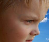 Child eye. Boy`s face close-up on blue sky stock photo