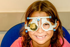 Child eye exam. Littlie girl is taking the eye exam test at optometrist office stock photos