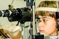 Child eye exam. Littlie girl is taking the eye exam test at optometrist office stock photo