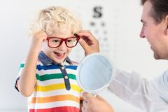 Child at eye sight test. Kid at optitian. Eyewear for kids. Royalty Free Stock Photo
