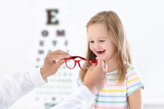 Child at eye sight test. Kid at optitian. Eyewear for kids. Child at eye sight test. Little kid selecting glasses at optician store. Eyesight measurement for Stock Photos