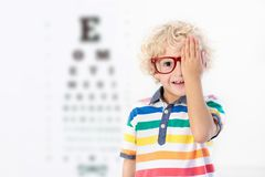 Child at eye sight test. Kid at optitian. Eyewear for kids. Child at eye sight test. Little kid selecting glasses at optician store. Eyesight measurement for Royalty Free Stock Photo