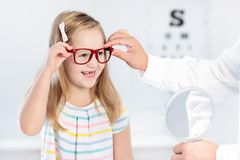 Child at eye sight test. Kid at optitian. Eyewear for kids. Child at eye sight test. Little kid selecting glasses at optician store. Eyesight measurement for Royalty Free Stock Images