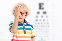 Child at eye sight test. Kid at optitian. Eyewear for kids. Stock Photos