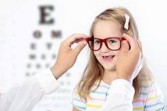 Child at eye sight test. Kid at optitian. Eyewear for kids. Child at eye sight test. Little kid selecting glasses at optician store. Eyesight measurement for Stock Photo
