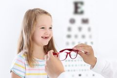 Child at eye sight test. Kid at optitian. Eyewear for kids. Child at eye sight test. Little kid selecting glasses at optician store. Eyesight measurement for Royalty Free Stock Image