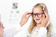 Child at eye sight test. Kid at optitian. Eyewear for kids. Child at eye sight test. Little kid selecting glasses at optician store. Eyesight measurement for Royalty Free Stock Photography