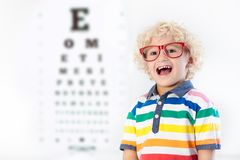 Child at eye sight test. Kid at optitian. Eyewear for kids. Child at eye sight test. Little kid selecting glasses at optician store. Eyesight measurement for Stock Images