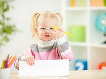 Child in eyeglasses drawing picture at home Stock Photography