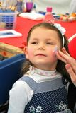 Child Face paining. Cute Little girl enjoying face painting Royalty Free Stock Photos