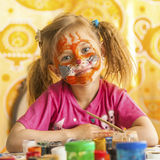 Child with a face painted with colorful paints. Fun. Royalty Free Stock Images