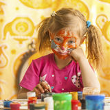 Child with a face painted with colorful paints (squares series). Fun Games royalty free stock photos