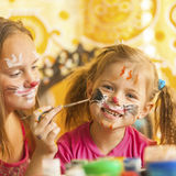 Child with a face painted with colorful paints. (squares series).Fun Games royalty free stock image