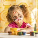 Child with a face painted with colorful paints (squares series). Small artist Stock Image