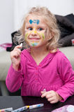 Child face painting. A pretty four-year-old girl shows off her face painting stock images