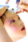 Child Face Painting. Little girl getting her face painted at a fair royalty free stock photography
