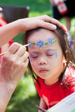 Child Face Painting. Child getting her face painted at the fair Royalty Free Stock Images