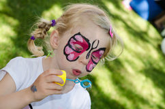 Child with face painting. Blond girl with face painting stock photography