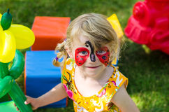 Child with face painting. Blond girl with face painting stock image
