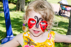 Child with face painting. Blond girl with face painting stock photo
