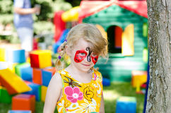Child with face painting. Blond girl with face painting royalty free stock photography