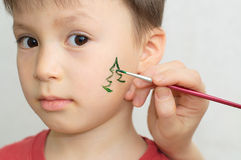 Child face painting. Caucasian boy child face painting for christmas party Stock Photography