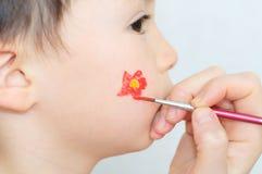 Child face painting flower. Caucasian boy child face painting  flower for party Royalty Free Stock Images