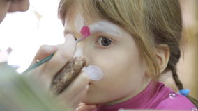 Child face painting like a cat stock video footage