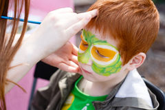 Child face painting process at redhead boy Stock Photo