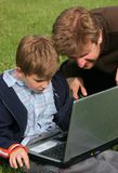 Child, fahter, laptop. Child is sitting with laptop in the park with his father Royalty Free Stock Photo