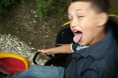 Child in fairground ride. Child on fairground rollercoaster travelling at speed sticking tounge out laughing. youth having fun at theme park ride Stock Photography