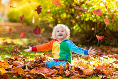Child in fall park. Kid with autumn leaves. Royalty Free Stock Images