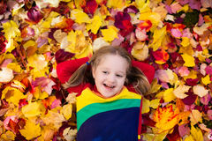 Child in fall park. Kid with autumn leaves. Royalty Free Stock Photos