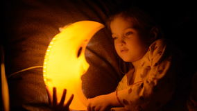 The child falls asleep under a lamp.
