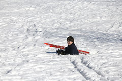 Child falls from skiing in winter Royalty Free Stock Photos
