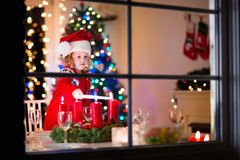 Child at family Christmas dinner at home. Christmas dinner at home. Child lighting a candle on advent wreath on Xmas eve. Decorated living room with fireplace Royalty Free Stock Photos