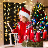 Child at family Christmas dinner at home. Christmas dinner at home. Child lighting a candle on advent wreath on Xmas eve. Decorated living room with fireplace Stock Photo
