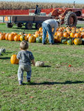 Child and farmer at pumpkin farm Royalty Free Stock Photos