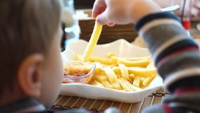 A child in a fast food cafe eating fried potatoes in a plate. Hand close up. Slices of potatoes, fried in oil stock footage