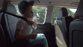 Child fastened with safety belt traveling bay car. Boy traveling on back seat of a car and fastened with safety belt. Kid looking through the windows on the way stock footage