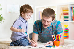 Child and father drawing with colourful pencils. Adorable kid child and his dad drawing with color pencils Stock Photo