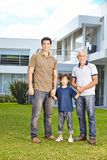 Child with father and grandfather in front of house. Happy child is standing with father and grandfather in front of house in the garden stock photo