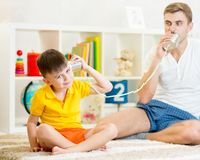 Child and father having a phone call with tin cans. Child and father plays having a phone call with tin cans Stock Photography
